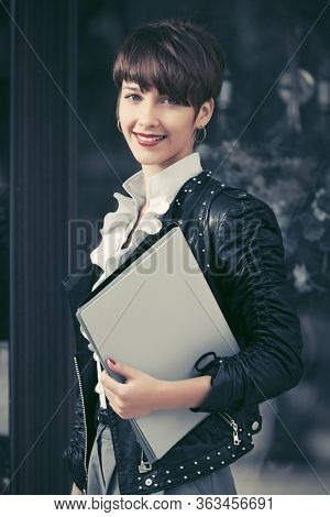 Happy young fashion business woman with file folder walking on city street Stylish trendy model with pixie hair in black leather jacket and white blouse