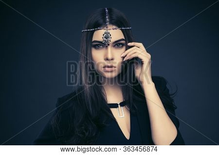Young fashion woman with long straight brown hairs on dark background Stylish female model in black blazer and top