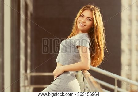 Happy young woman leaning on railing Stylish fashion model in gray crop top and skirt suit