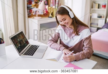Young Female Student Sitting At The Table, Using Laptop When Studying.