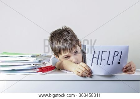 Sad Tired Frustrated Kid Sitting At The Table With Many Books And Holding Paper With Word Help. Lear