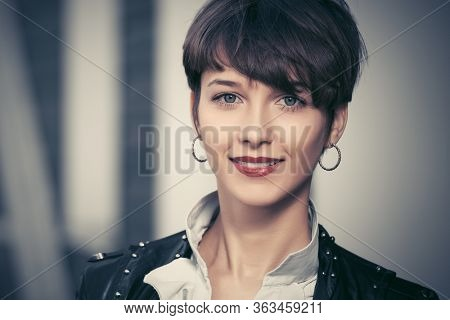 Happy young fashion woman walking on city street Stylish female model in black leather jacket with pixie hair style