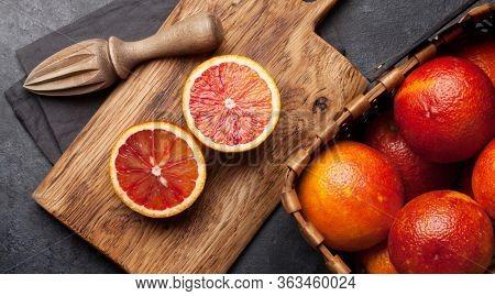 Sicilian Blood juicy oranges in basket and juicer. Top view