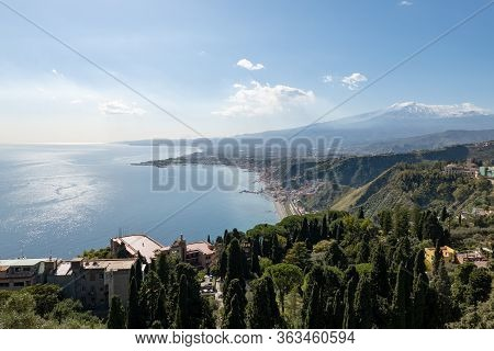 Taormina City, Coastline And Blue Sea In Sicily, Italy With Etna Volcano In The Background