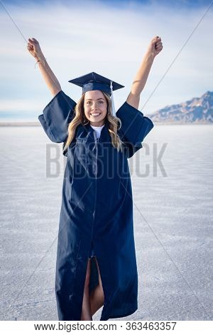 Cute Young woman in her graduation cap and gown showing excitement after graduating. Beautiful girl showing real emotion after finishing her degree