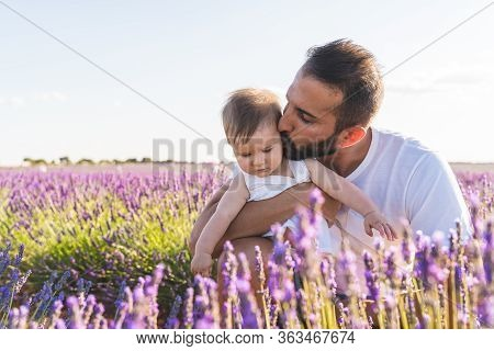 Spanish Father With His Daughter Having Fun In A Field Of Flowers.
