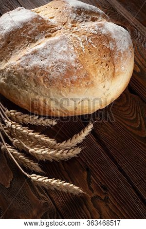 Homebaked Bread. Peasant Round Bread And Wheat Spikelets On A Wooden Background. Homemade Baking.