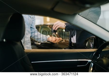 Close-up Of Car Salesman Handing Over Keys For New Car To Young Man Buyer In Auto Dealership, View F