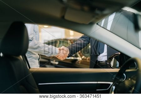 Buyer Of Car Shaking Hands With Seller In Auto Dealership, View From Interior Of Car. Close-up Of Ha