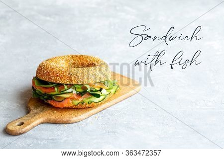 Sandwich with red fish on the board.Proper nutrition.Red fish.Making a sandwich.burger with fish. Ch
