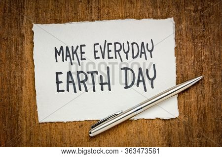 make everyday earth day inspirational note - handwriting on white handmade rag paper against dark papyrus background, environmental concept
