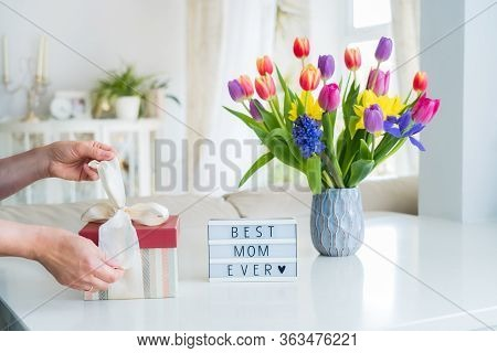 Female Hands Are Opening Gift Box On Marble Table With Colorful Spring Flowers Bouquet In Vase And L