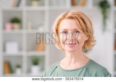Smiling mature woman with under eye patches looking at you while standing in front of camera on background of shelves with flowerpots and books