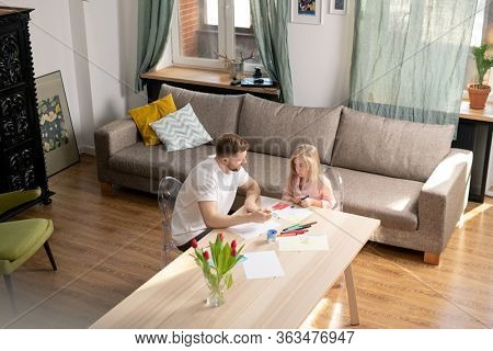 Cute little girl with crayon or highlighter looking at her father and listening to him while both sitting by table and drawing in living-room