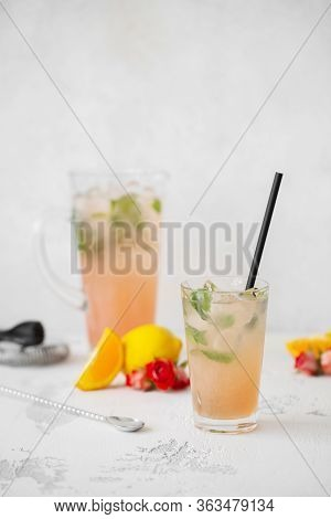Summer Refreshing Cocktail With Tea Rose Petals, Lemon And Mint. Refreshing Drink In A Glass On A Li