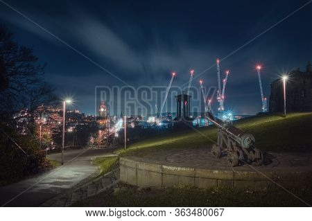 Night View Of The City Of Edinburgh From Calton Hill. In The Foreground Is An Old Cannon. The Portug