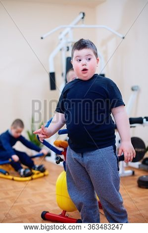 Cute Kid With Down Syndrome At Inclusive Sport Center For Kids With Special Needs. Living A Full Lif
