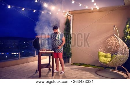 Adult Man Grilling The Barbecue On Rooftop Terrace At Home In The Evening