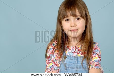 Sweet little girl 6-7 years old posing in dungarees jeans and flower pattern blouse on blue background. Isolateded studio portrait.