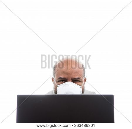 African American Man With Medical Mask Looking Over Laptop Computer. Concept Of Lockdown, Flatten Th
