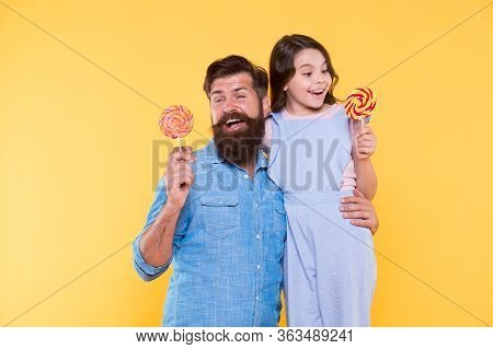 Daughter And Father Eat Sweet Candy. Bearded Man And Cute Sweet Baby. Loving Daddy And Small Girl Ea