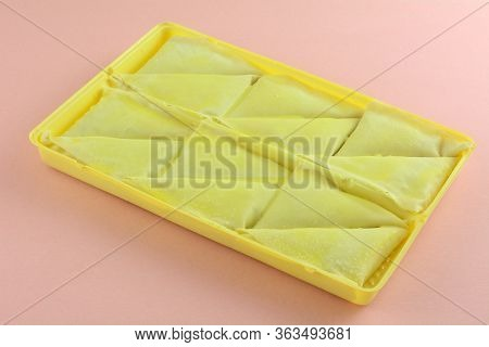 Frozen Spanakopita Triangle Appetizers In Yellow Packaging On Pink Background