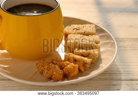Sweet Rice Puffs Blocks And Fried Dough Twists And Peanut Brittles And Cup Of Coffee On A Dish