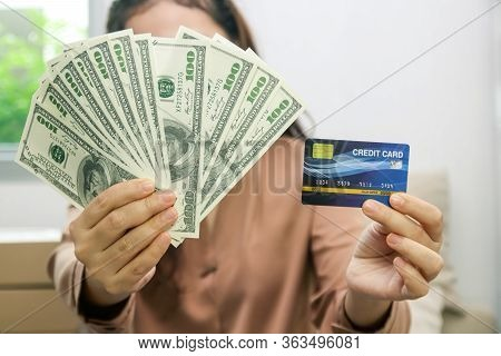 The Woman Who Runs Online Business Holds Money And Mockup Credit Cards. Glad To Succeed. Startup Con