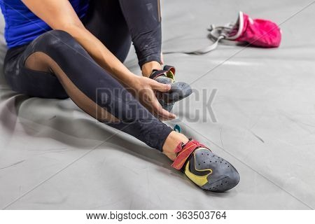 Rock Climber Woman Sitting On A Bouldering Climbing Wall Holl, Inside On Colored Hooks