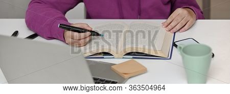 Close Up View Of College Student Reading Book To Prepare Her Seminar