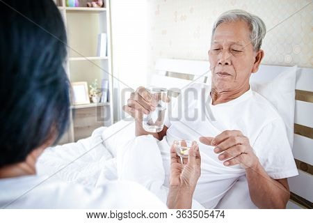 Elderly Asian Couples Taking Care Of Each Other The Husband Is Sick, The Wife Gives Medicine And Dri