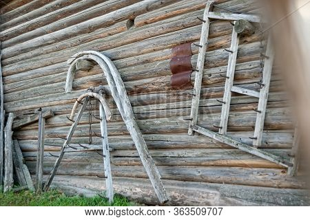 The Ancient Wooden Tools Of Peasant Labor Hang On The Wooden Wall Of The House