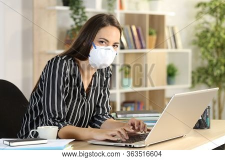 Teleworker In Covid-19 Confinement Wearing Protective Mask With Laptop Looking Camera Sitting On A D