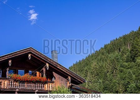 Chalet With Flowers On The Balcony In Tyrol, Austria In Summer