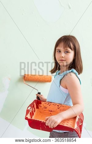 Kid Standing With Paint Roller In Hand. She Is Painting The Wall. Redecoration, Repair And Repaint C