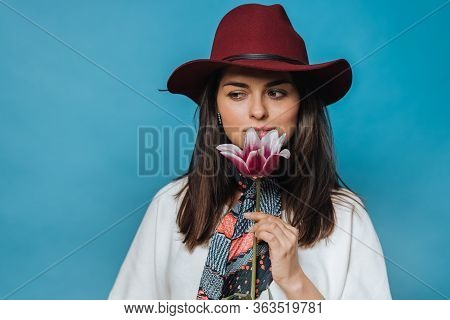Attractive Young Lady Holds Flower, Looking Aside, Dressed In White Sweater, Burgundy Hat With A Bri