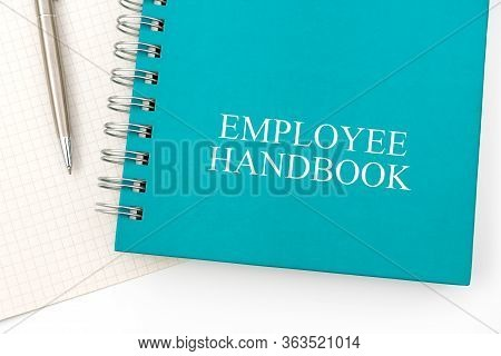 Employee Handbook Or Manual With A Pen And Paper On A White Table In An Office - Personnel Managemen