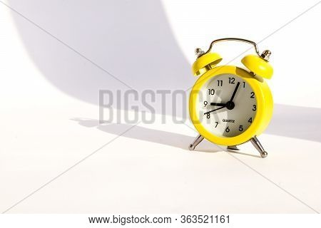 Yellow Alarm Clock On White Background, Copy Space, Cute Yellow Metal Alarm Clock With Large Shadow