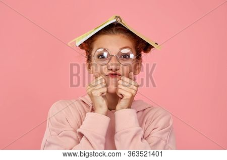 Horizontal Shot Of Anxious Ginger Female Fooling Around With Bewilderment, Has Textbook On Head, Loo