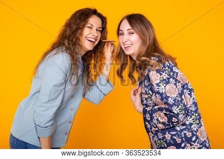 Two Funny Female Friends Or Sisters Eating Sharing Cookie On Yellow Background. Friendship, Relation
