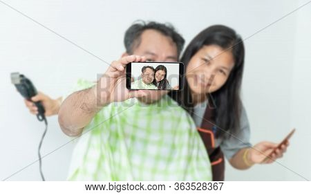 The Husband And Wife Are Taking The Selfie ,while Cutting His Hair