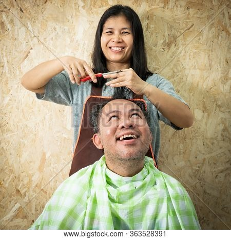 Wife Cutting Hair For Her Husband , With A Happy Posture ,stay At Home