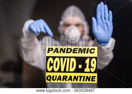 Man In Protective Suit And In Protective Medical Mask Showing Stop Gesture. Epidemiologist Show Stop