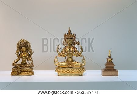 Gilded Statues Of The Chenrezi, The Tara And Stupa Arranged In A Row On The Altar. The Gilded Four-a