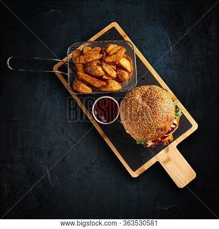 Tasty Burger And Golden Potatoes With Bbq Sauce On Dark Background