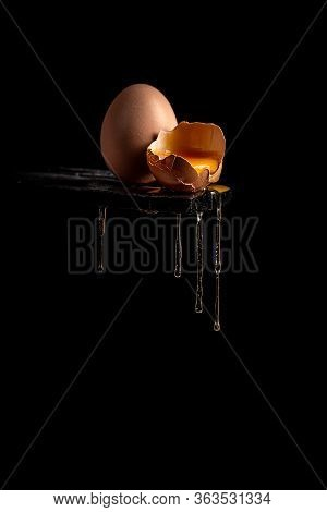 Concept Image Of A Broken Brown Egg Shell With Dripping Egg White On Black Background