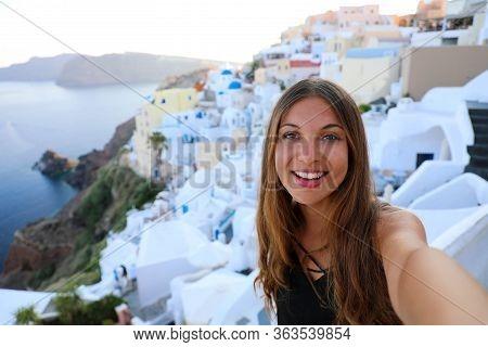 Self Portrait Of Smiling Girl In Oia Village, Santorini, Greece. Happy Tourist Girl Taking Selfie Pi