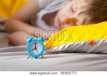 Child Sleeping In Bed On Pillow With Alarm Clock In The Morning. Focus On Alarm Clock