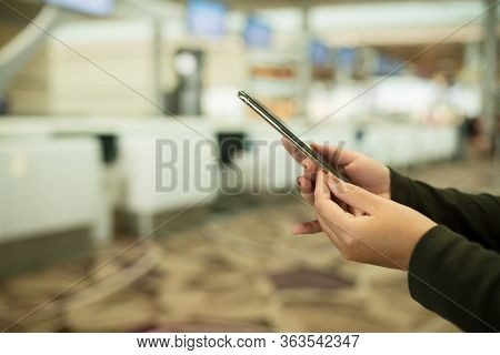 People Hands Use Cellphone At Counter Check-in Airport On Background With Bokeh, Check Flight Number