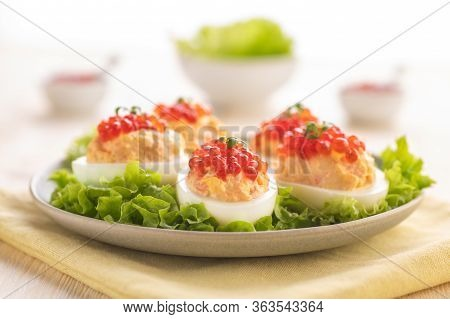 Stuffed Eggs With Red Caviar. Traditional Festive Russian Snack. A Large Portion Is Served On A Whit